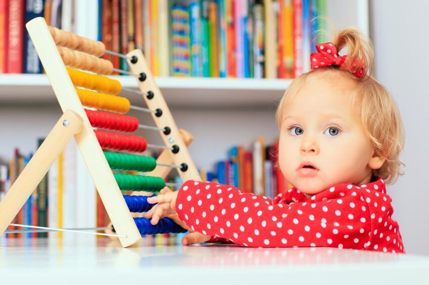 little girl playing with abacus, early learning concept